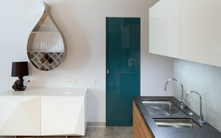<p>Автор проекта: ANC Concept</p> <p>В белой аскетичной кухне акценты расставлены забавным дизайном и модным цветом. На фоне белых стен отлично выглядят узкая стекляная дверь цвета морской волны, оригинальный стеллаж каплевидной формы и черная лампа-заяц от голландской Moooi. </p>