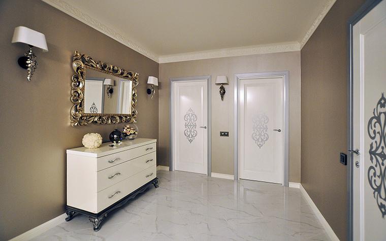 <p>Автор проекта: Студия tutto design</p> <p>Просторный холл декорирован в стиле современной классики. На фоне светло горчичных стен хорошо смотрятся большое зеркало в золоченой раме и серия классических бра с белыми абажурами. </p>
