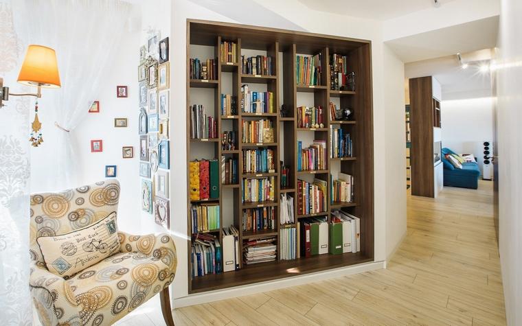<p>Автор проекта: Старикова Ольга</p> <p>Небольшая библиотека организована в проходной зоне. Для этого&nbsp; на одной из стен оборудовали открытый стеллаж из темного дерева, а рядом разместили кресло с настенным светильником. </p>